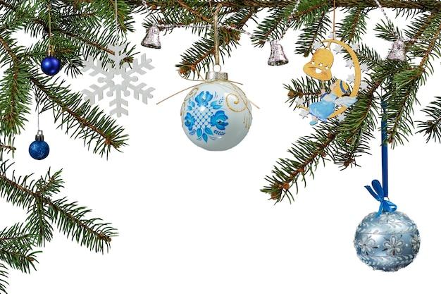 Takken van dennenboom met speelgoedballen, klokken en andere kerstversiering op een witte geïsoleerde achtergrond.