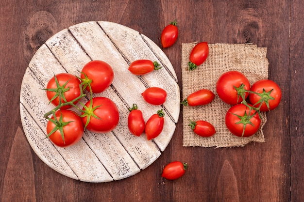 Takken van kersentomaten op houten raad dichtbij de tomaten op jute op houten