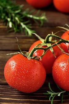Takken van rijpe rode tomaten en takken van rozemarijn op donkere houten muur. close-up, selectieve aandacht. tomaten in druppels water. natuurlijk vers voedsel van de markt om de lekkerste gerechten te bereiden