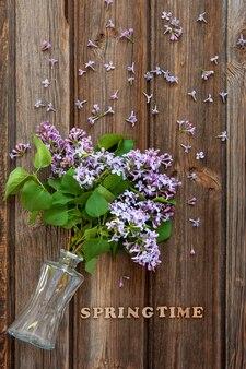 Takken van verse geurige lila in glazen fles op een vintage houten tafel. close-up, bovenaanzicht, flatlay