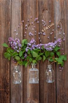 Takken van verse geurige lila in glazen flessen op een vintage houten tafel. close-up, bovenaanzicht, flatlay