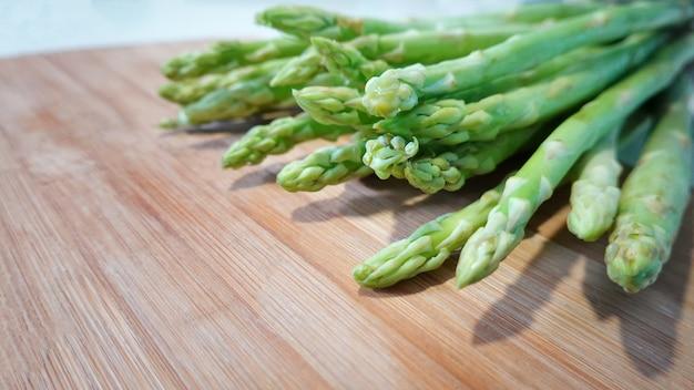 Takken van verse groene asperges op hout, vergrote weergave.