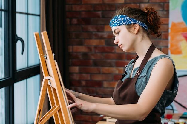 Talent en vaardigheden. zijaanzicht van creatieve vrouwelijke kunstenaar die ezel gebruikt voor het schilderen van abstracte kunstwerken.