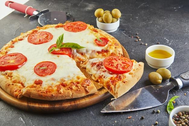 Talian pizza en ingrediënten voor het koken op een zwarte betonnen achtergrond