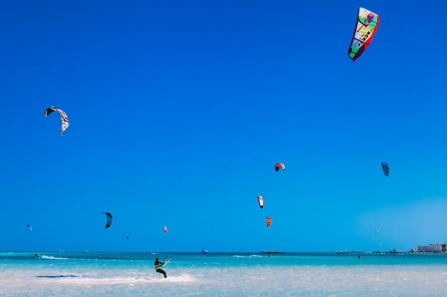 Talrijke vliegers in de blauwe lucht boven de rode zee.