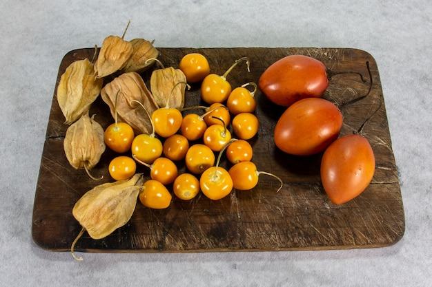 Tamarillo of boomtomaat op houten plank naast uvilla of aguaymanto physalis Premium Foto
