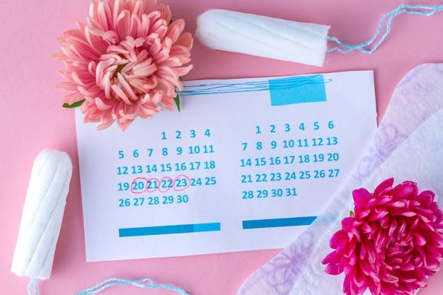Tampons en pads voor de menstruatie, dameskalender en bloemen. hygiëne zorg tijdens kritieke dagen. regelmatige menstruatiecyclus