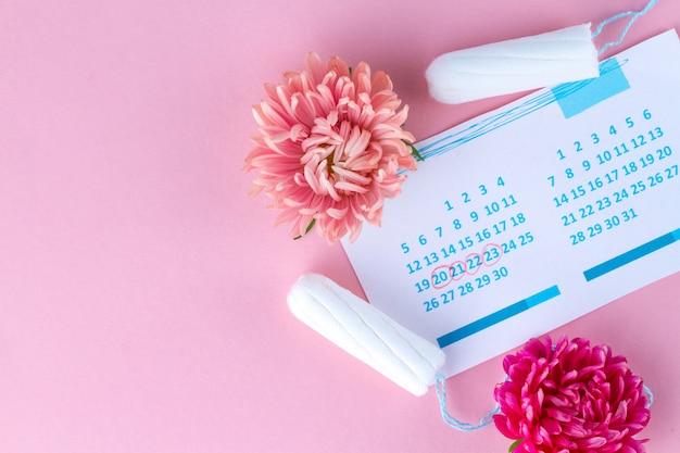 Tampons voor menstruatie, dameskalender en bloemen. hygiëne zorg tijdens kritieke dagen. regelmatige menstruatiecyclus