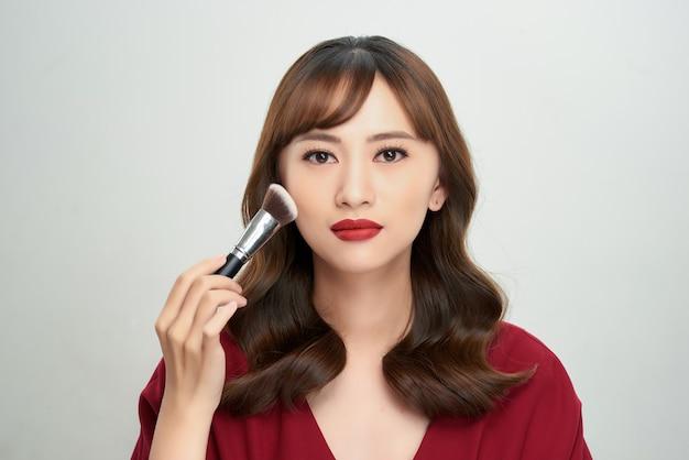 Tan huid van het schoonheids aziatische meisje met make-upborstels. ze glimlachte en kijkt naar poederborstel, natuurlijke make-up