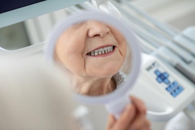 Tand herstel. senior vrouw die in de spiegel kijkt na een bezoek aan het kantoor van tandartsen