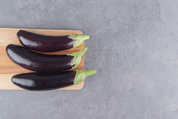 Tandachtige aubergine op het bord, op het marmeren oppervlak