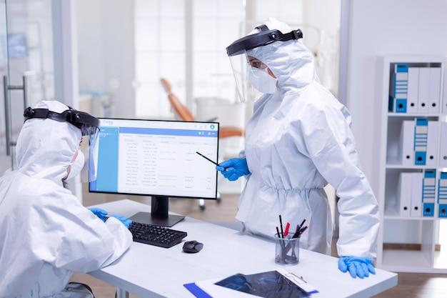 Tandarts-arts die een ppe-pak draagt, praat met een verpleegster bij de receptie over het schema van de patiënt. medicijnteam dat als veiligheidsmaatregel beschermingsuitrusting draagt tegen een pandemie van het coronavirus bij de tandheelkundige receptie.