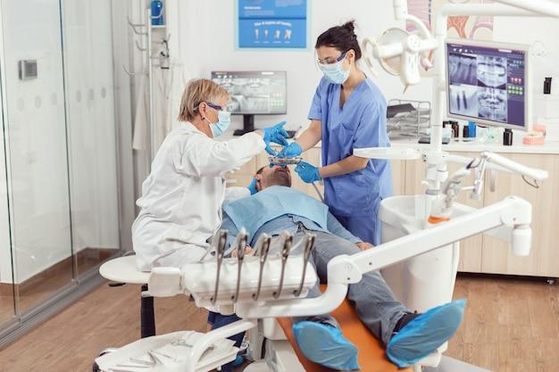 Tandarts arts en medisch verpleegkundige maken professionele tandenreiniging aan zieke man patiënt tijdens stomatologisch onderzoek in tandartspraktijk. ziekenhuisteam dat kiespijn onderzoekt en tandbehandeling voorbereidt