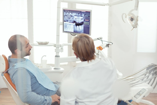 Tandarts arts en patiënt kijken naar digitale teeh x-ray in stomatologie ziekenhuis kantoor. zieke patiënt zittend op een tandartsstoel die zich voorbereidt op tandheelkunde tijdens een somatologische afspraak
