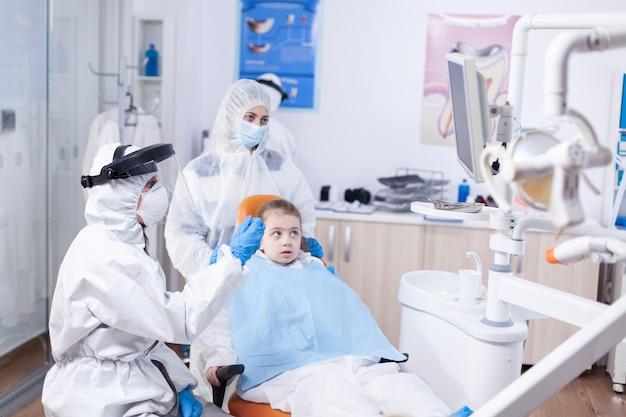 Tandarts arts in de cursus klein kind overleg in tandheelkunde kantoor. stomatoloog in beschermpak voor coroanvirus als veiligheidsmaatregel met röntgenfoto's van kindertanden tijdens consultatie.