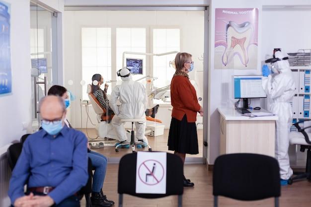 Tandarts arts in pbm-pak die patiënt in tandheelkundige kliniek raadpleegt, gekleed in pbm-pak als veiligheidsmaatregel tijdens wereldwijde pandemie met coronaivurs