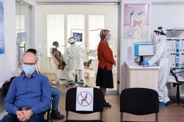 Tandarts arts in pbm-pak die patiënt in tandheelkundige kliniek raadpleegt, gekleed in pbm-pak als veiligheidsvoorzorg...