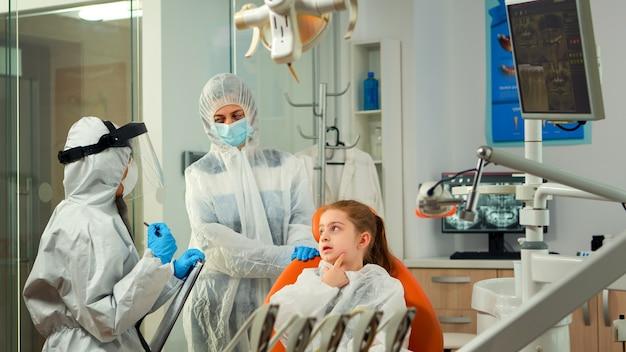 Tandarts-arts in ppe-pak die de patiënt van het kind ondervraagt en aantekeningen maakt op het klembord terwijl het meisje de aangetaste massa aangeeft. stomatoloog en assistent werken in een nieuwe normale tandartspraktijk met overall