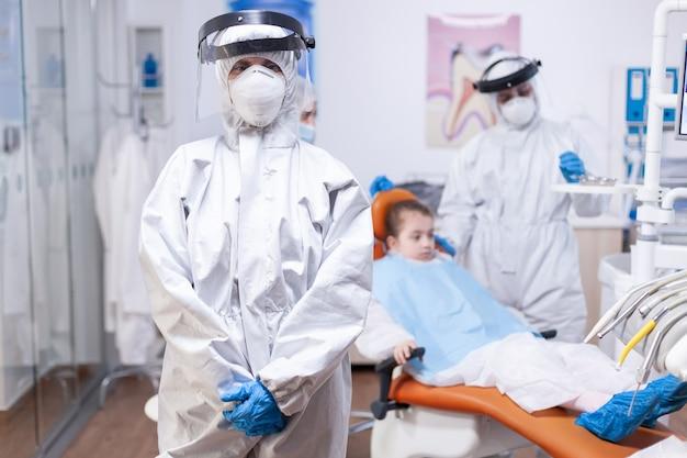 Tandarts arts kijkt naar camera met gezichtsmasker in de loop van covid19 pandemie. portret van een vermoeide stomatoloog die een coronavirus ppe-pak draagt en naar de camera kijkt. Premium Foto