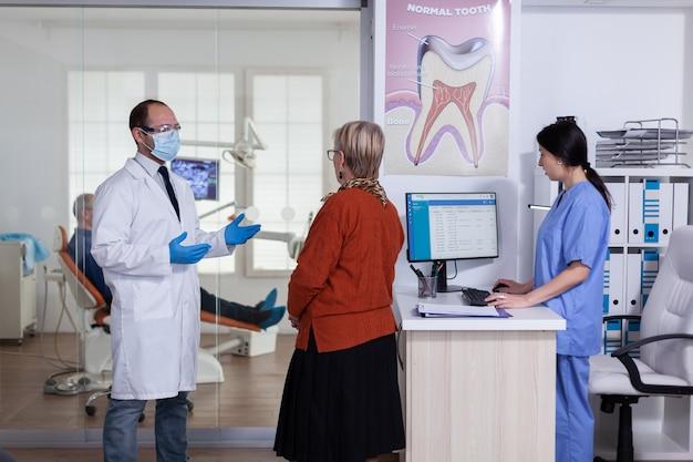 Tandarts arts met gezichtsmasker diagnose uit te leggen aan senior vrouw patiënt in stomatologie wachtruimte hal. oudere man zittend op een stoel voor de behandeling van tanden.