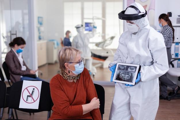 Tandarts-arts met gezichtsschild wijzend op tablet-display en tandheelkundige röntgenfoto's uit te leggen aan senior patiënt tijdens wereldwijde pandemie