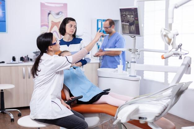 Tandarts-arts wijzend op cariës op het scherm van de tandartsstoel in de loop van een consult voor een klein kind. stomatoloog die de diagnose van tanden uitlegt aan moeder van kind in gezondheidskliniek met röntgenfoto.