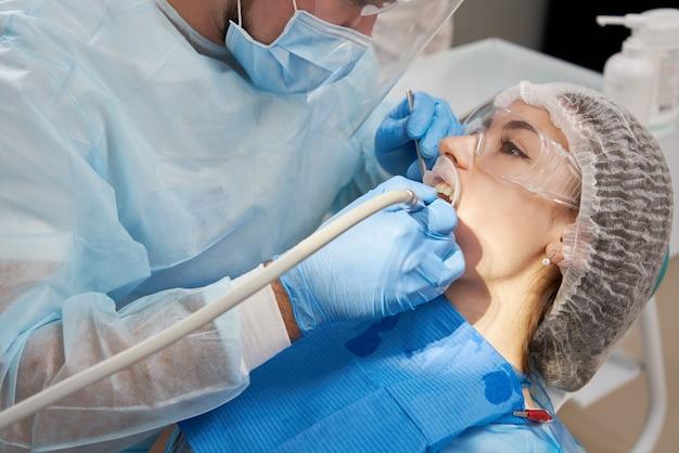 Tandarts boortand aan mannelijke patiënt in tandartsstoel