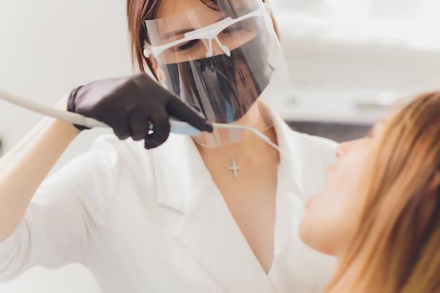 Tandarts detecteert de carieuze tanden van de patiënt op de tandartsstoel.