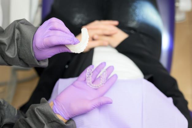 Tandarts die aan vrouwenpatiënt een orthodontische siliconetrainer toont. mobiel orthodontisch apparaat voor gebitscorrectie.