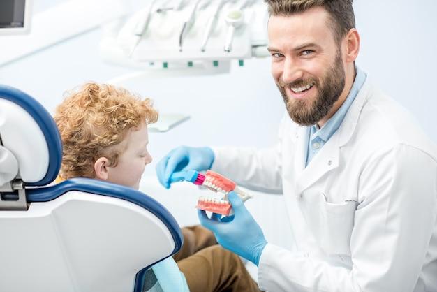 Tandarts die de jongen laat zien hoe hij tanden poetst op een kunstmatige kaak bij de tandartspraktijk