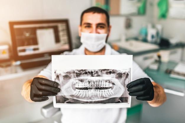 Tandarts die de röntgenstraal van de patiënt in de tandkliniek toont