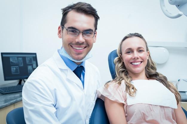 Tandarts die de tanden van de jonge vrouw onderzoekt