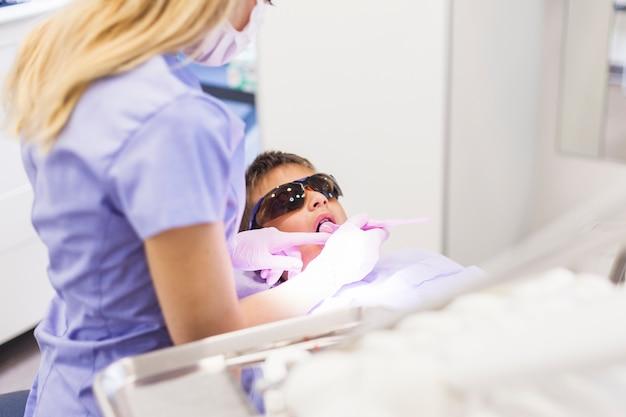 Tandarts die de tanden van de jongen met tandspiegel controleert