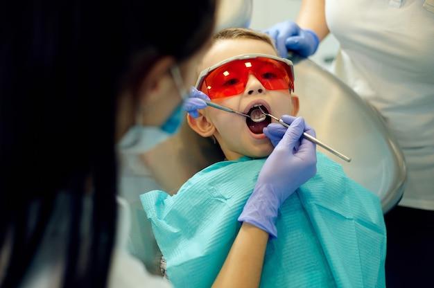 Tandarts die de tanden van de kleine jongen in de kliniek onderzoekt. een kleine jongen die mond opent bij een tandenbehandeling