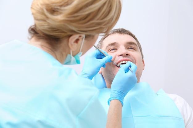 Tandarts die de tanden van de patiënt in de kliniek onderzoekt