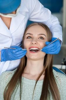 Tandarts die de tanden van een patiënt in de tandarts onderzoeken.