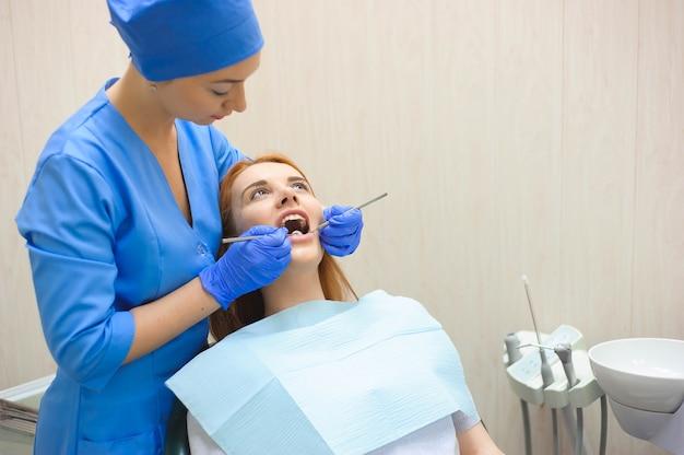 Tandarts die de tanden van een patiënt in de tandarts onderzoekt.