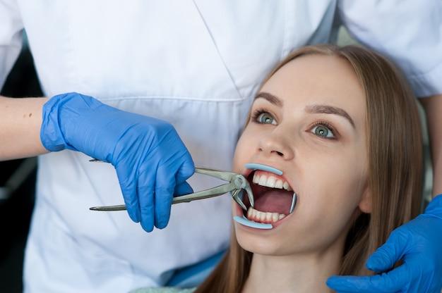 Tandarts die de tanden van een patiënt in de tandkliniek onderzoeken.