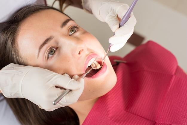 Tandarts die de tanden van een vrouwelijke patiënt in het tandartskantoor onderzoeken