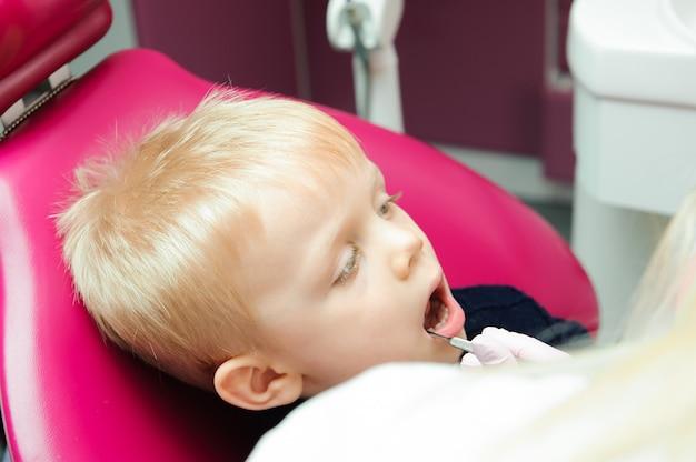 Tandarts die de tanden van het jonge geitje onderzoeken bij tandkliniek