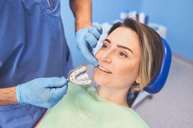 Tandarts die de tandlepel van de materiaalimpressie in tandheelkundebureau gebruiken