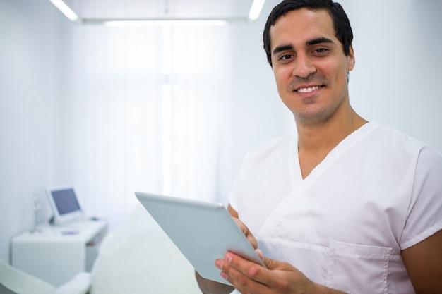 Tandarts die een digitale tablet gebruiken bij kliniek