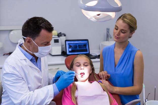 Tandarts die een jonge patiënt met hulpmiddelen onderzoekt