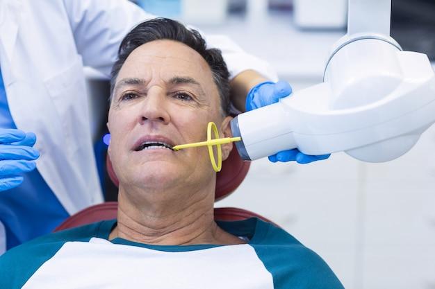 Tandarts die een mannelijke patiënt met hulpmiddel onderzoekt