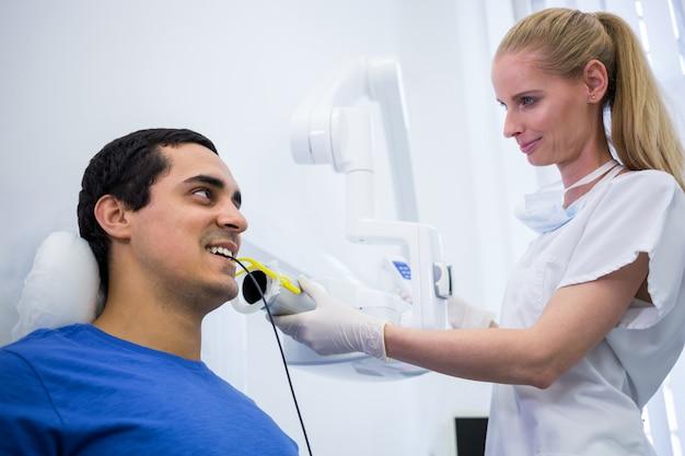 Tandarts die een mannelijke röntgenstraal van de patiëntentand nemen