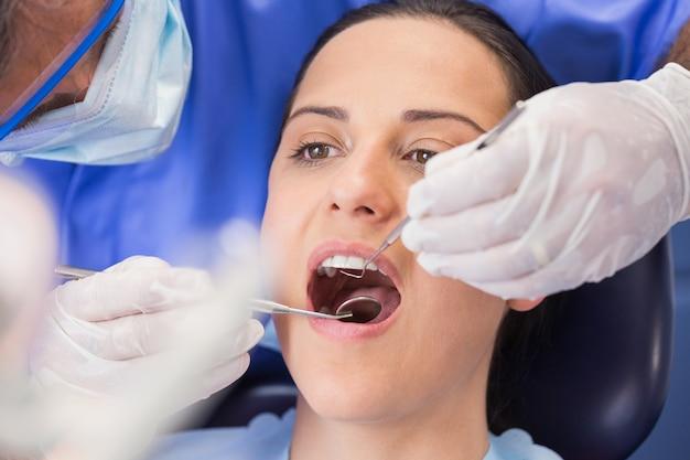 Tandarts die een patiënt met hoekspiegel en sikkelstift onderzoekt
