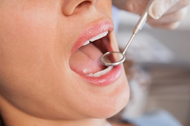 Tandarts die een patiëntentanden onderzoeken als tandartsenvoorzitter