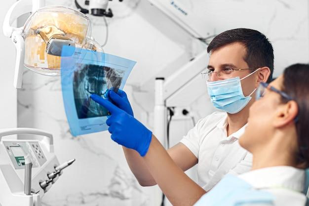 Tandarts die een röntgenfoto met een patiënt bekijkt.