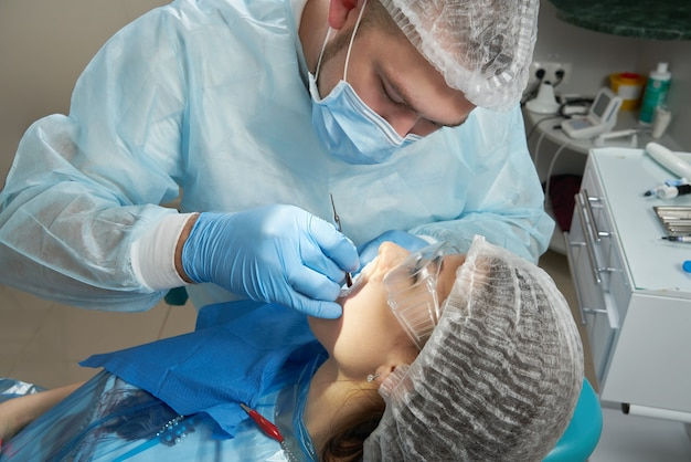 Tandarts die een tandheelkundige behandeling op een vrouwelijke patiënt doet. tandarts behandeling van de tanden van een patiënt in moderne tandheelkunde kantoor