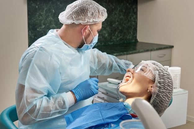 Tandarts die een tandheelkundige behandeling op een vrouwelijke patiënt doet. tandarts die de tanden van een patiënt in modern onderzoekt